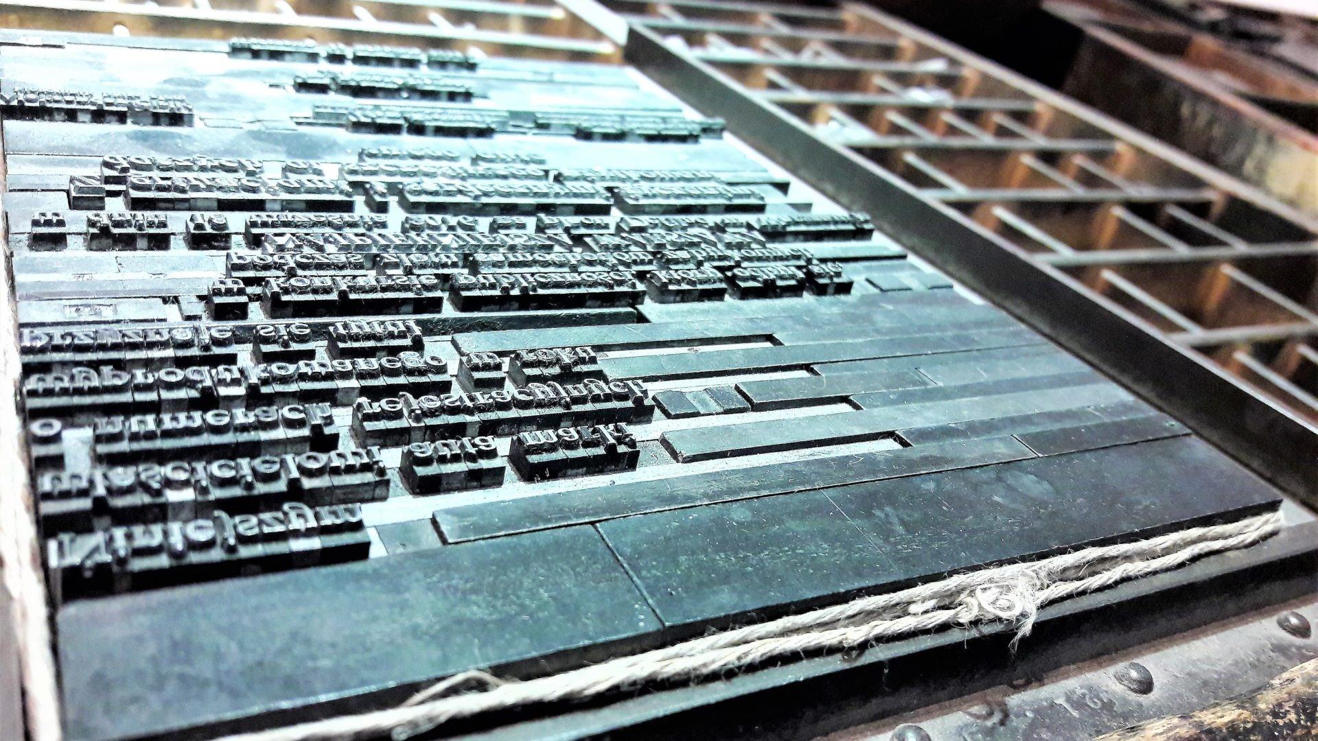 Skład drukarski ułożony na drewnianej szufloramie, związany sznurkiem. Skład przygotowany do druku. Fot. Muzeum Drukarstwa